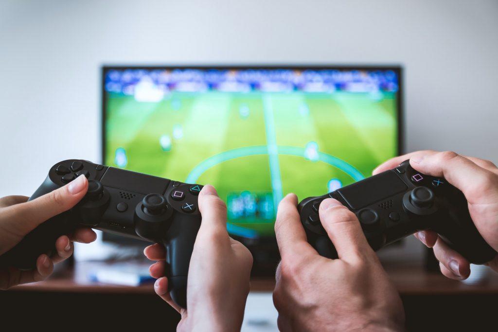 Foto com duas mãos brancas segurando controle de videogame, ao fundo uma TV desfocada aparecendo um jogo de futebol.